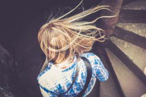Blonde Frau läuft die Treppen nach unten
