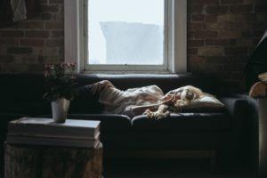 frau liegt erschöpft auf der couch